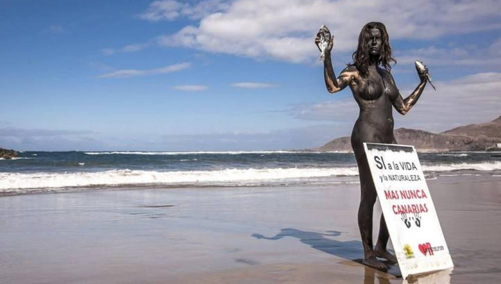 Una activista desnuda y pintada de negro para denunciar los riesgos del petróleo