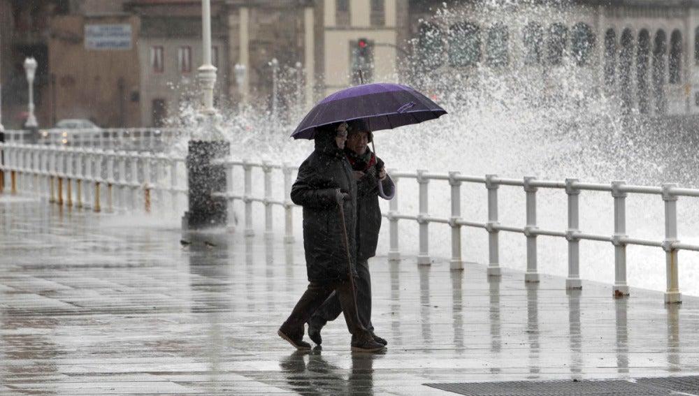 Dos personas pasean por Gijón bajo la lluvia