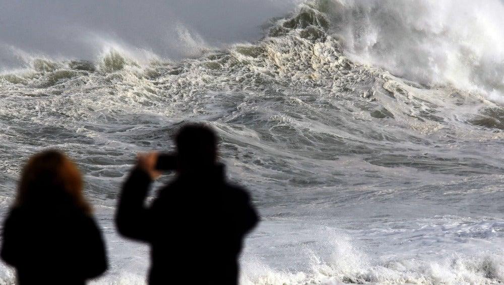 Dos personas fotografían el fuerte oleaje