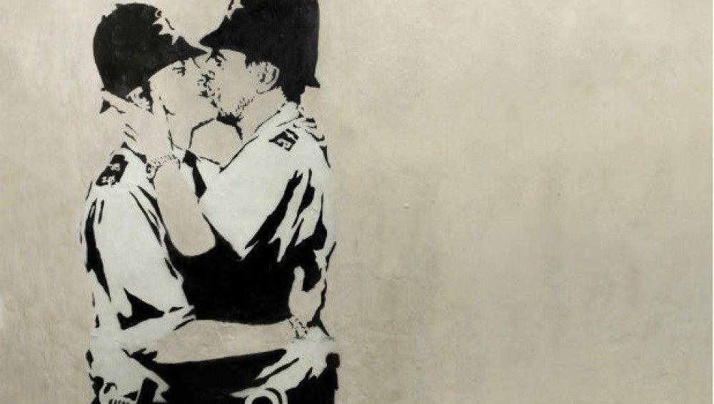 Obra de Banksy en blanco y negro, en la que aparecen dos policía británicos besándose.