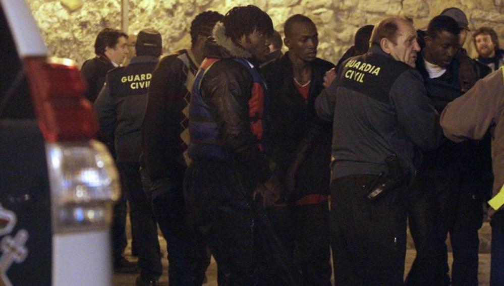 Miembros de la Guardia Civil atienden a algunos de los quince inmigrantes