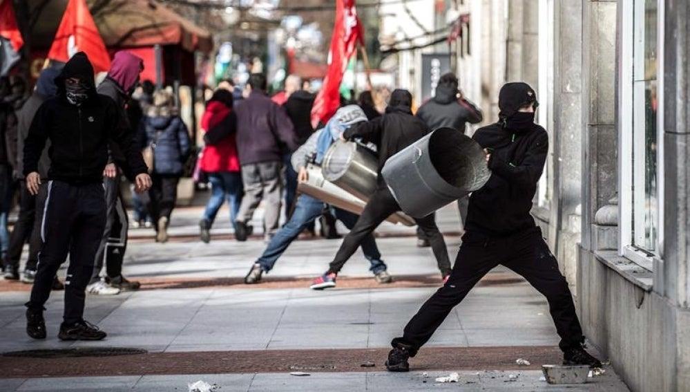 Encapuchados destrozan escaparates en la manifestación en protesta por el foro económico en Bilbao