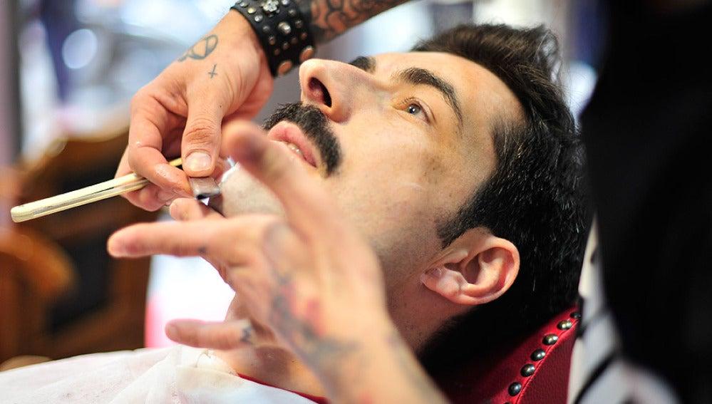 Un hombre afeitándose en una barbería