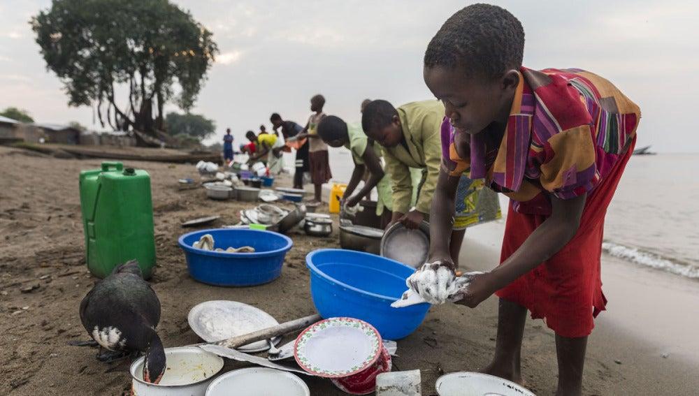 Un niño lava platos junto a un lago en el Congo