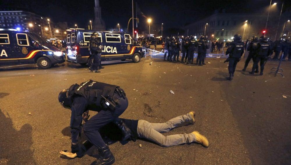 Un Policía detiene a una persona tras la Marcha por la Dignidad