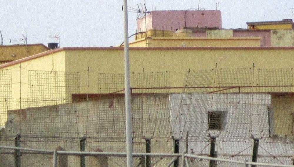 Un inmigrante subido en una farola de Melilla