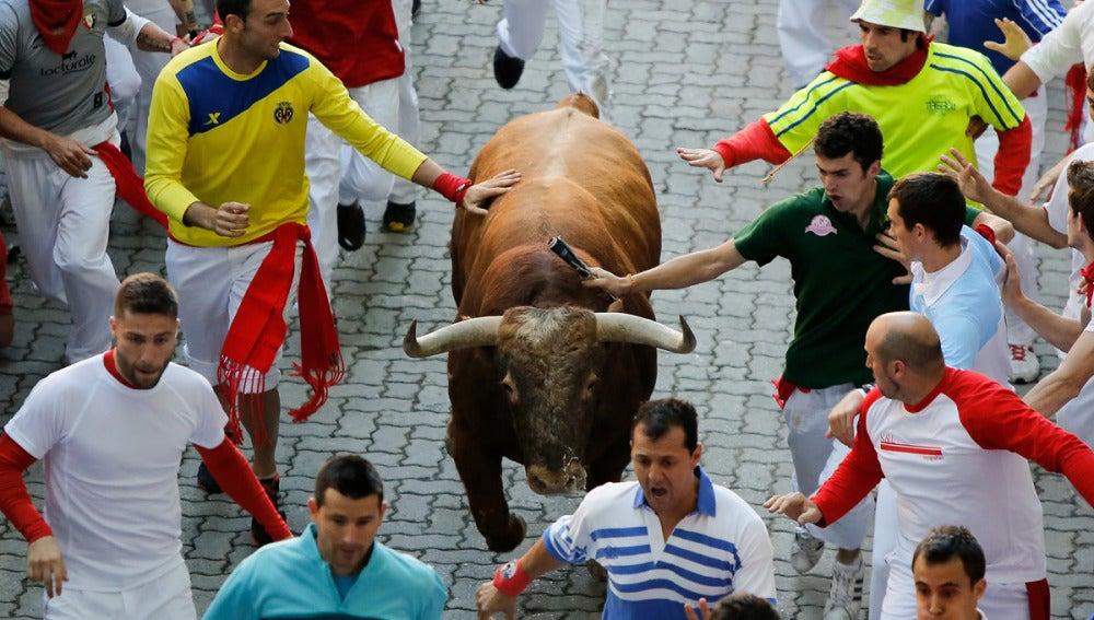 Dos mozos tocan a un toro durante un encierro de San Fermín