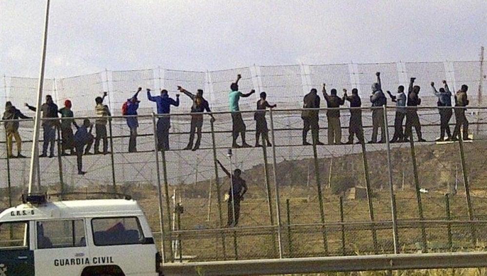 Decenas de inmigrantes, encaramados en la valla de Melilla