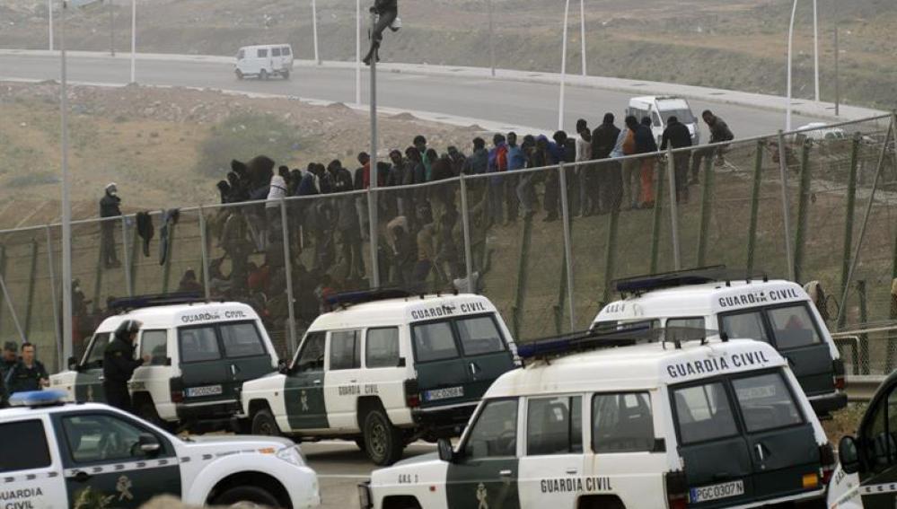 Fuerte presencia de la Guardia Civil mientras los inmigrantes subsaharianos permanecían encaramados a la valla de Melilla