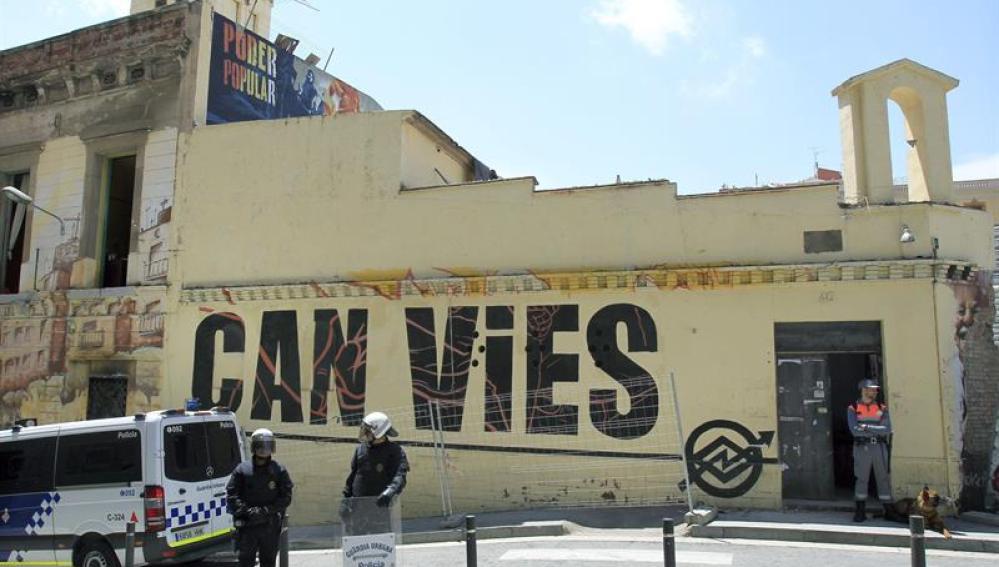Agentes vigilan el acceso al inmueble Can Vies, en Barcelona