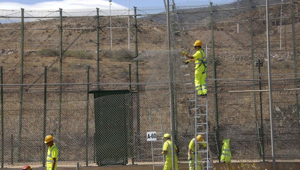Un grupo de operarios repara el tramo de valla por donde han saltado más de 500 inmigrantes