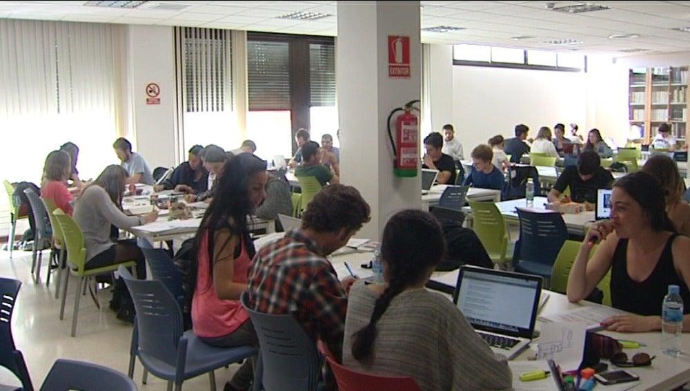Estudiantes repasan apuntes en una biblioteca