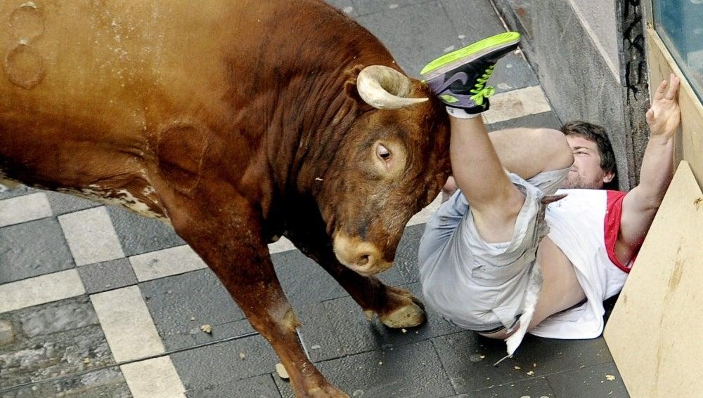 Un corredor embestido varias veces por un toro