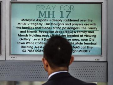 """Un pasajero observa una pantalla en la que se lee """"Rezo por MH17"""""""