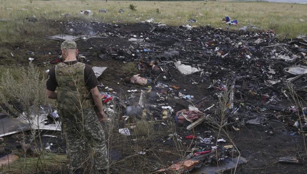 Un rebelde prorruso observa varios cadáveres entre los restos del avión Boeing 777 del vuelo MH17