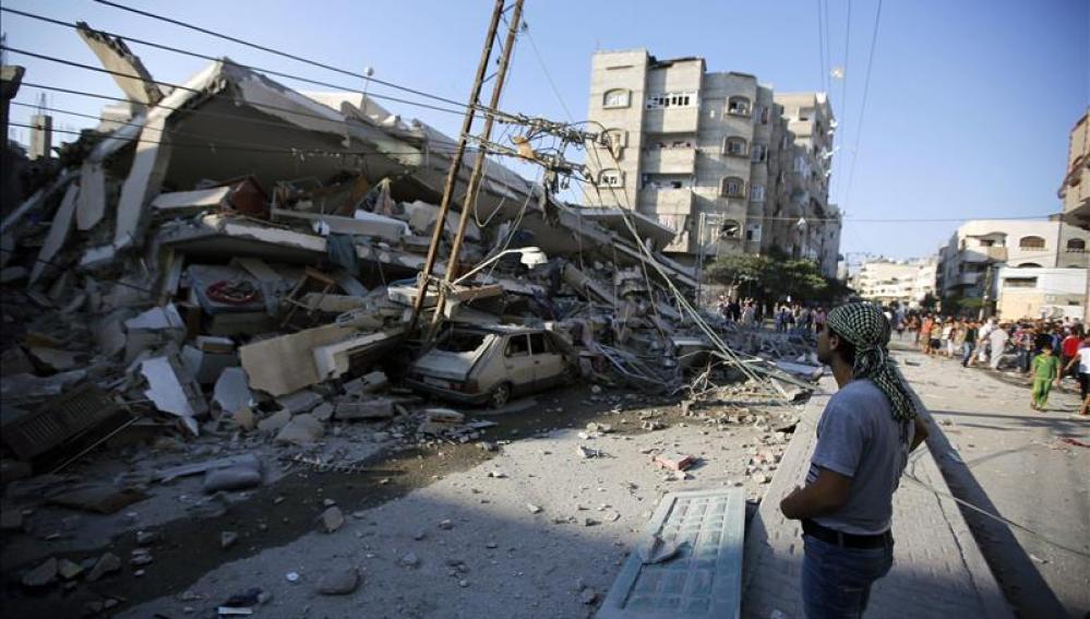Unos palestinos observan un edificio destruído por proyectiles en Gaza