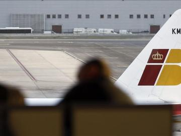 Dos pasajeros contemplan un avión de Iberia