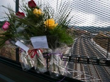 En la verja que da a la curva de A Grandeira se agolpan flores en recuerdo de las víctimas