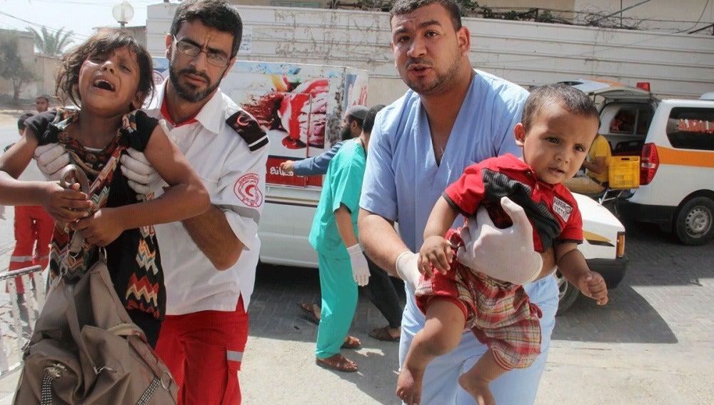 Palestinos llevan a unos niños heridos en brazos a un hospital