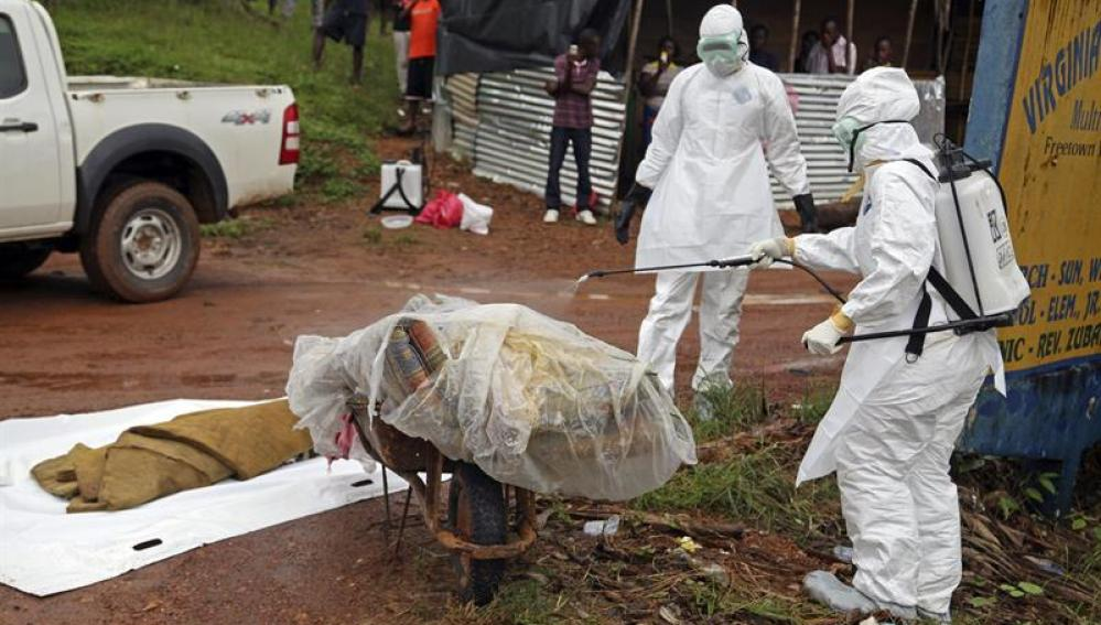 Varias enfermeras desinfectan una víctima del ébola en la calle