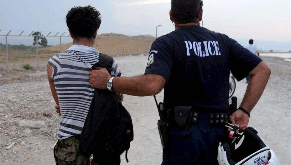 un policía griego con un inmigrante ilegal en la localidad de Kandare