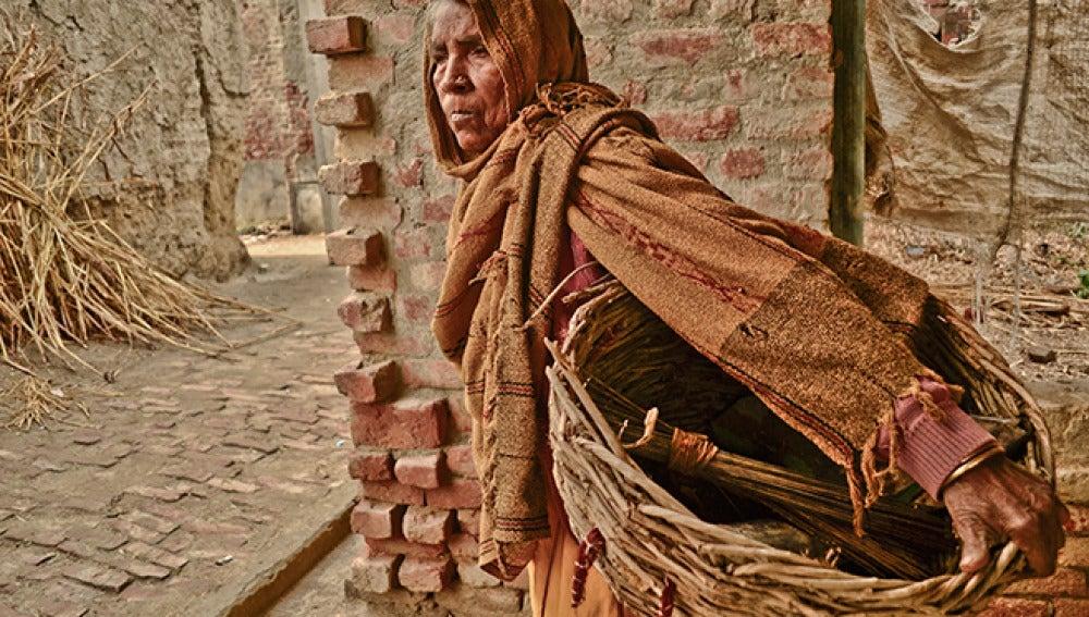 Una mujer limpia excrementos humanos de sanitarios secos en Kasela