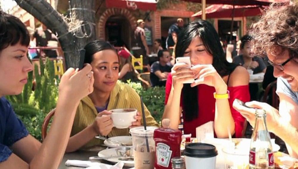 Tres personas consultan su teléfono móvil durante una comida