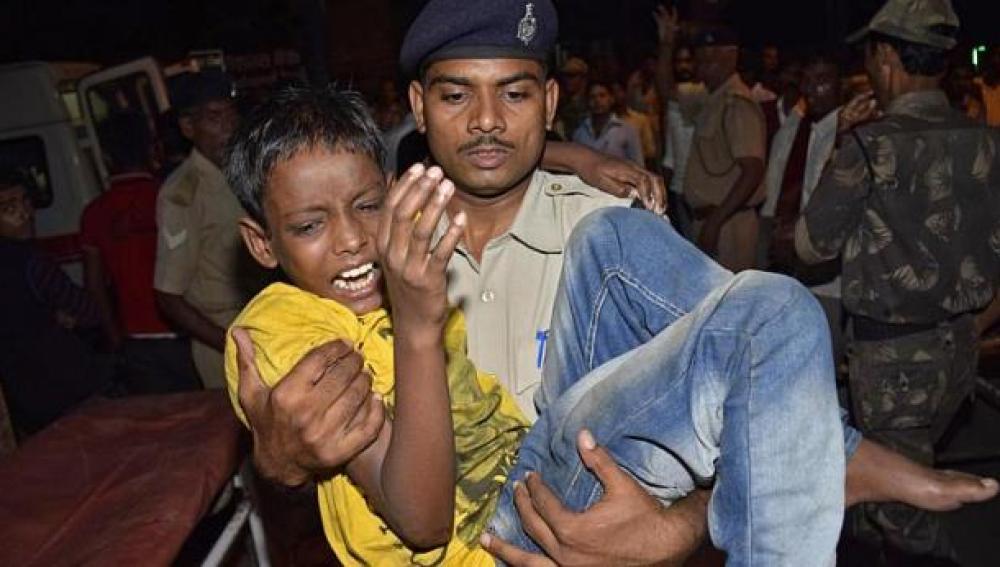 Un policía lleva a un niño herido