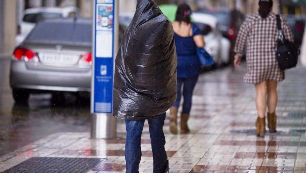 Se resguarda de la lluvia bajo una bolsa