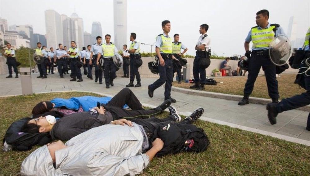 Activistas prodemocráticos descansan ante las autoridades.