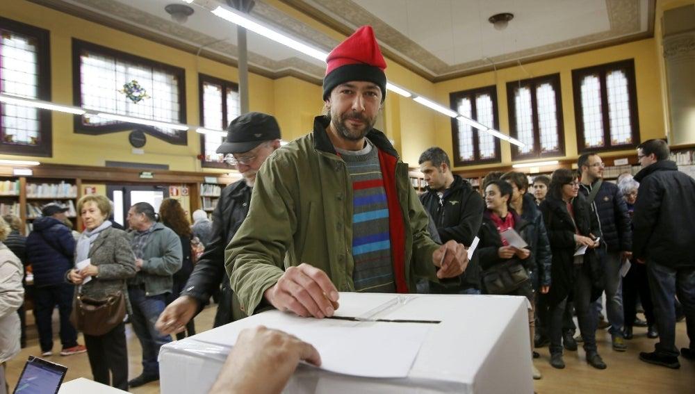 Un ciudadano, con barretina, deposita su papeleta