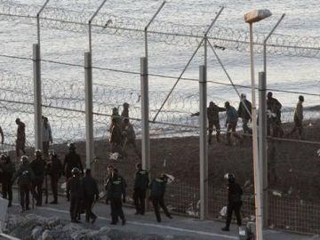 Las fuerzas españolas de seguridad e inmigrantes a ambos lado de la valla de Ceuta