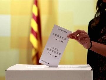 Una persona introduce una papeleta en una urna el 9N