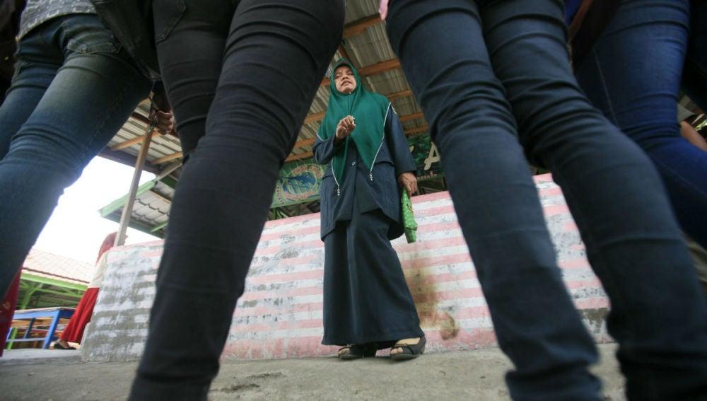 Una policía indonesia reprende a un grupo de mujeres