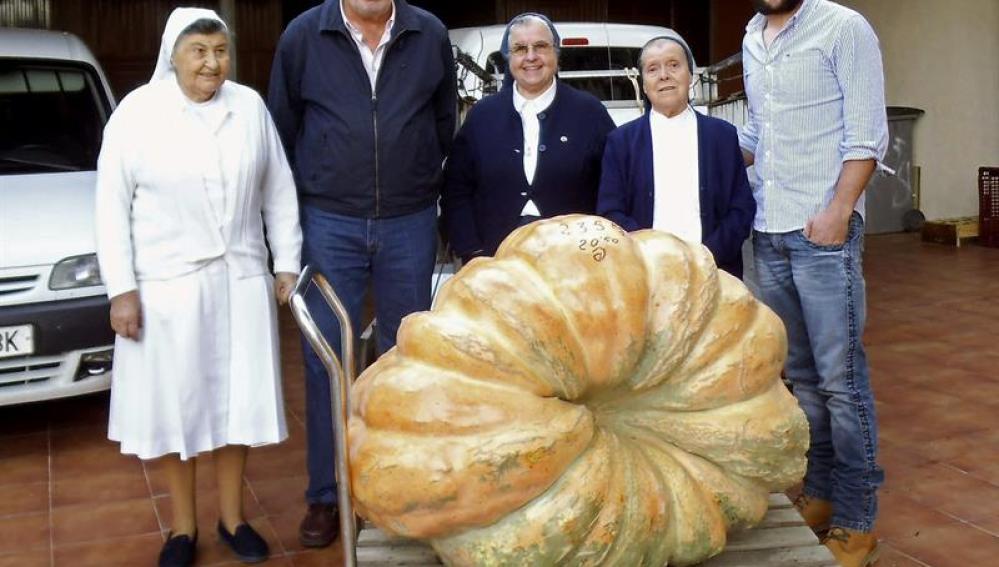El agricultor posa con la calabaza y los gestores del Banco de Alimentos