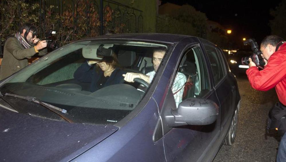 Un coche traslada a uno de los tres sacerdotes y al seglar detenidos