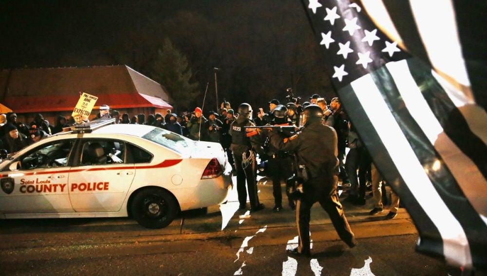 Un agente dispara en mitad de los disturbios en Ferguson