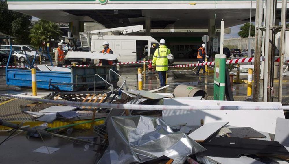 Empleados de una gasolinera retiran los desperfectos causados tras los fuertes vientos
