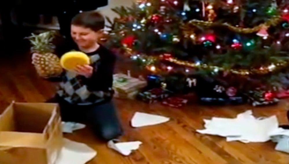 Un niño recibe una piña por Navidad
