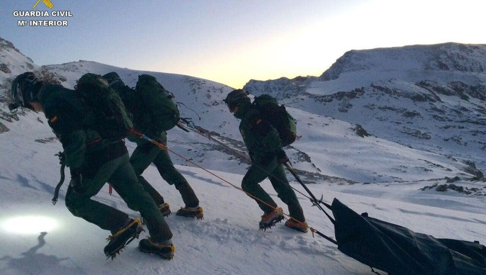 Agentes de la Guardia Civil arrastran el cuerpo de la alpinista fallecida en Sierra Nevada