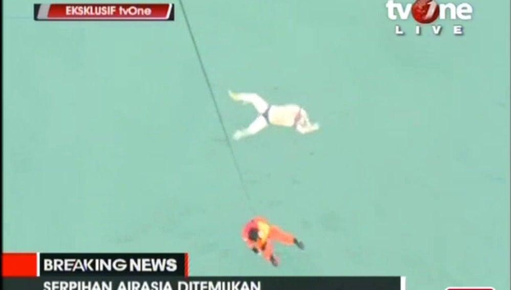 Un operario baja a rescatar un cuerpo de una víctima del avión de AirAsia
