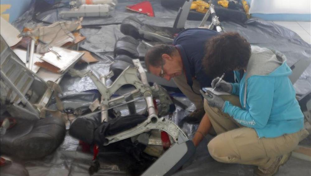 Especialistas revisan una silla del avión siniestrado.