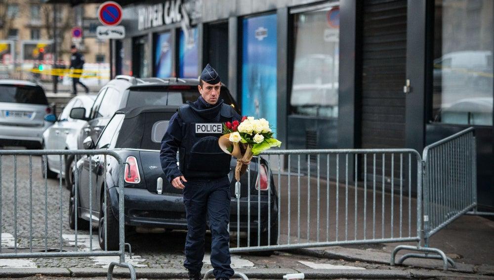 Un Policía deja flores en el 'Hyper Cacher'