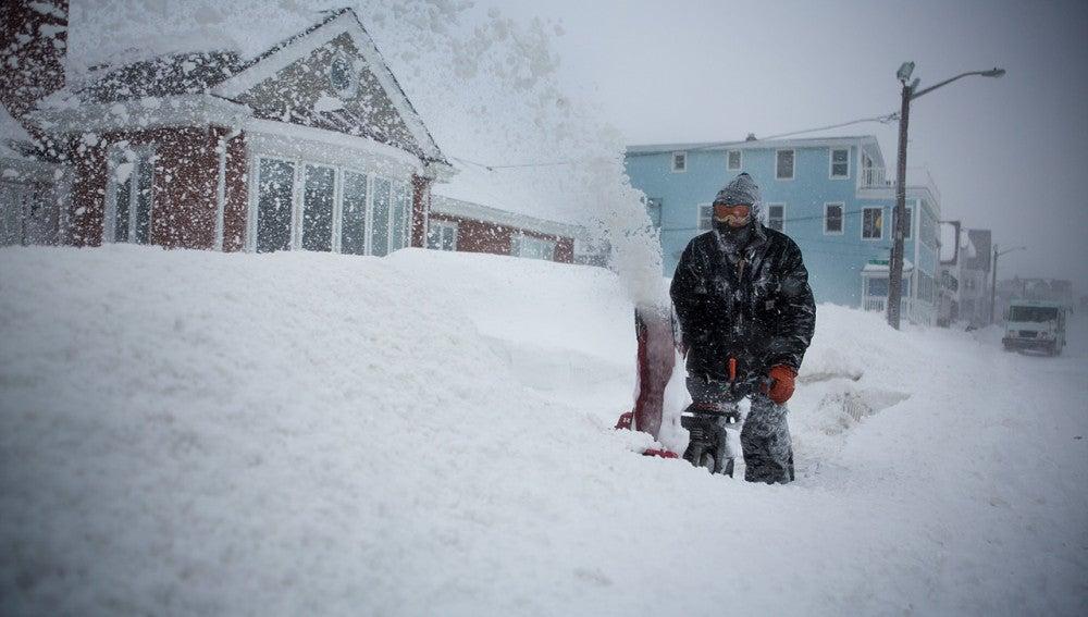 Un hombre retirando nieve frente a su casa