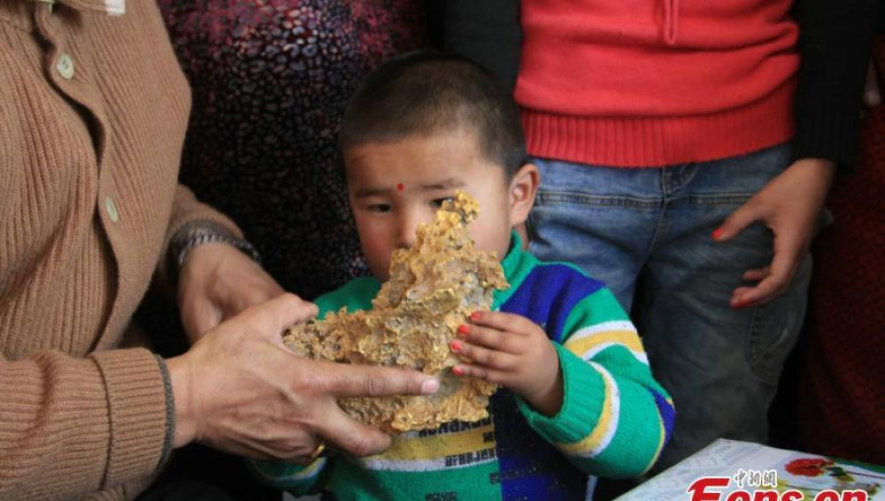Un niño sostiene la pepita de oro