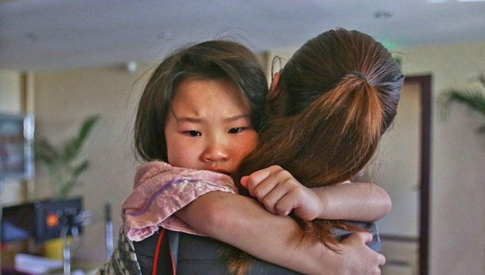 La pequeña Siyao en brazos de una empleada