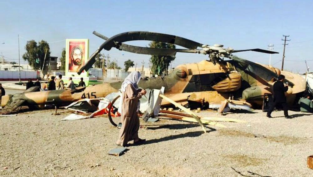 Sodados iraquíes revisan un helicóptero abatido en confrontaciones con EI