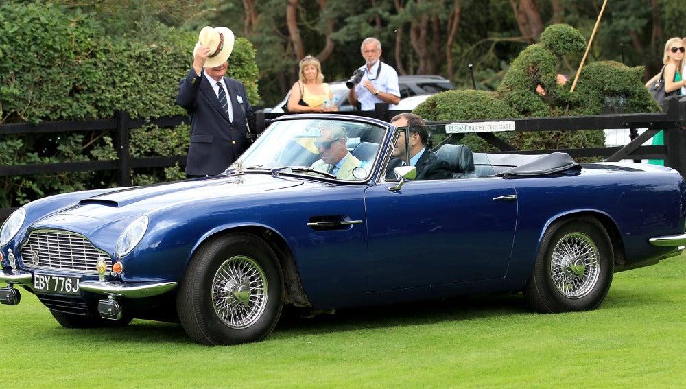 El príncipe Carlos de Inglaterra llega a un evento en un Aston Martin