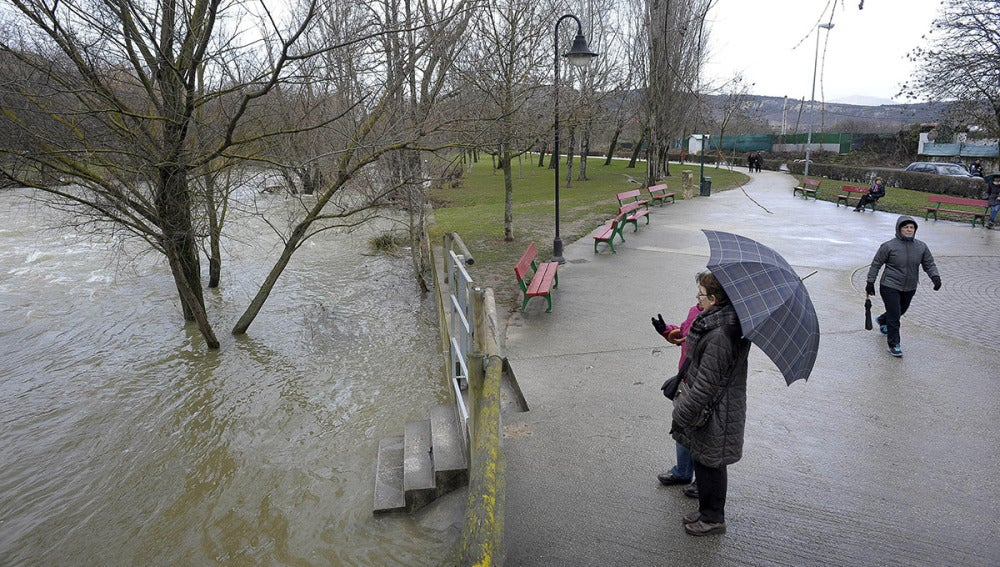 Viandantes miran la crecida del Ebro