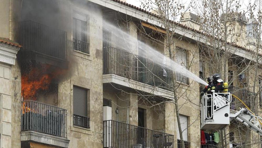 Efectivos del cuerpo de bomberos apagan las llamas de la vivienda